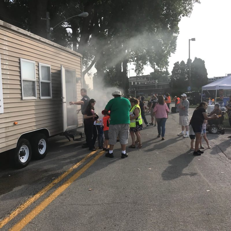 Firemen and Citizens Gathered on a Street by a Mobile Home