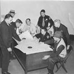 Photo of Officers reviewing pistol league targets.